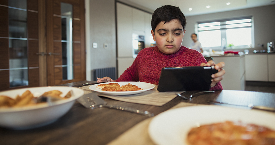 A photo of a boy eating looking at his tablet.