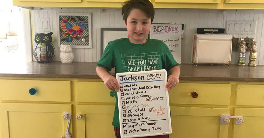 A photo of a boy holding up a list of activities