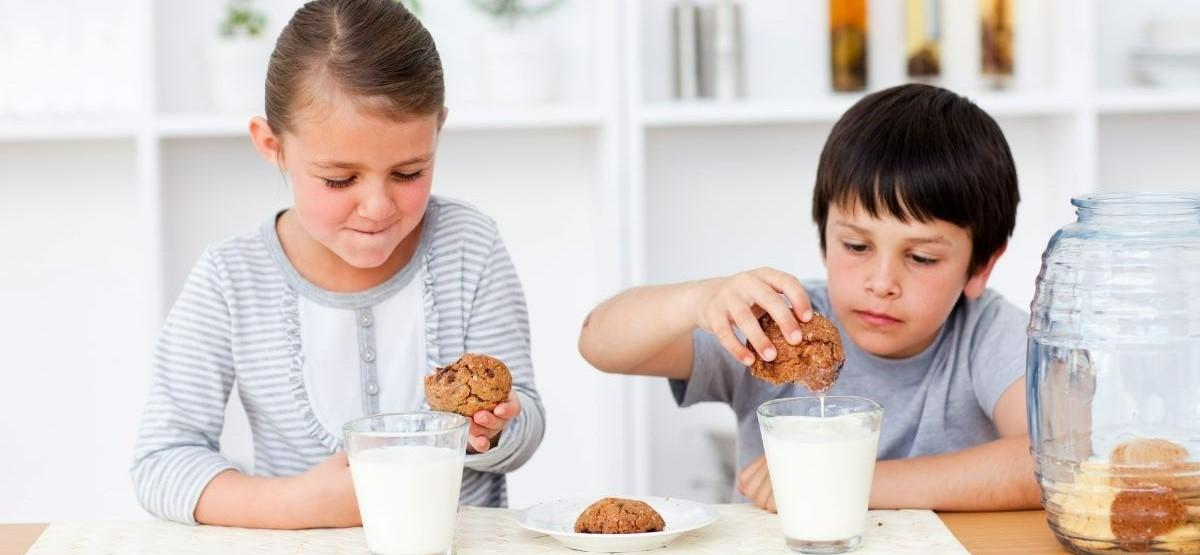 Photo of two children enjoying cookies and milk